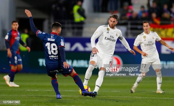 Sergio Ramos of Real Madrid competes for the ball with Pablo Insua of SD Huesca during the La Liga match between SD Huesca and Real Madrid CF at...