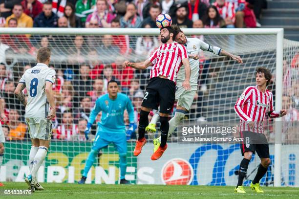 Sergio Ramos of Real Madrid competes for the ball with Raul Garcia of Athletic Club during the La Liga match between Athletic Club Bilbao and Real...