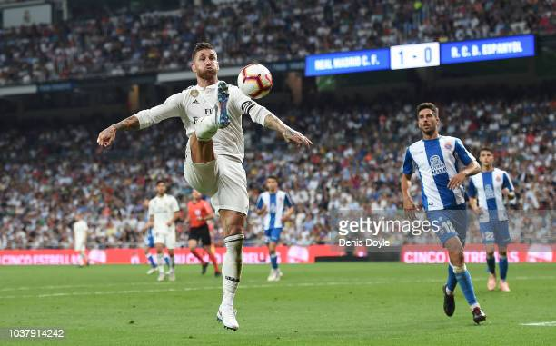 Sergio Ramos of Real Madrid controls the ball beside while Didac Vila of RCD Espanyol looks on during the La Liga match between Real Madrid CF and...