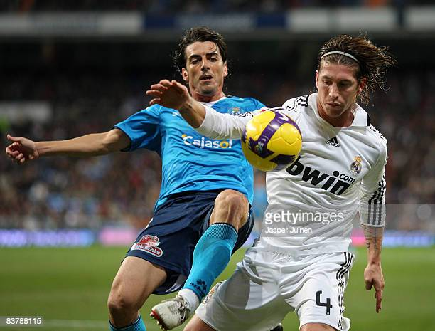 Sergio Ramos of Real Madrid duels for the ball with Francisco Javier Garcia of Recreativo Huelva during the La Liga match between Real Madrid and...