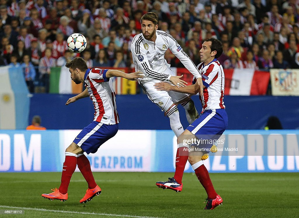 Sergio Ramos of Real Madrid heads the ball against Diego Godin (R) and Guilherme Siqueira of Atletico de Madrid during the UEFA Champions League Quarter Final first leg match between Club Atletico de Madrid and Real Madrid CF at Vicente Calderon Stadium on April 14, 2015 in Madrid, Spain.