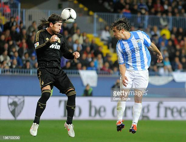 Sergio Ramos of Real Madrid heads the ball before Sebastian Fernandez of Malaga during the round of 16 Copa del Rey second leg match between Real...