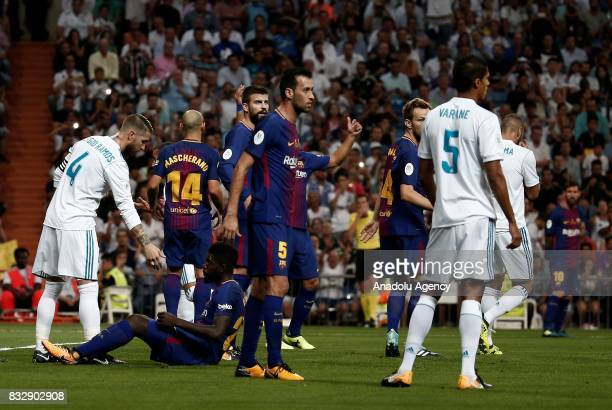 Sergio Ramos of Real Madrid helps Samuel Umtiti of Barcelona up after they argued during the Spanish Super Cup return match between Real Madrid and...