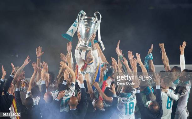 Sergio Ramos of Real Madrid holds up the trophy during celebrations at the Santiago Bernabeu stadium following their victory last night in Kiev in...