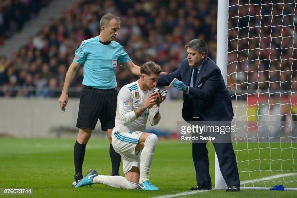 Sergio Ramos of Real Madrid is assisted after being injured during the match between Atletico Madrid and Real Madrid as part of La Liga at Wanda...