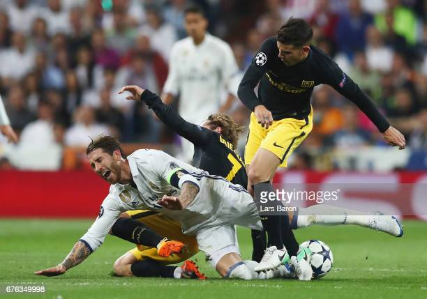 Sergio Ramos of Real Madrid is challenged by Antoine Griezmann and Lucas Hernandez of Atletico Madrid during the UEFA Champions League semi final...