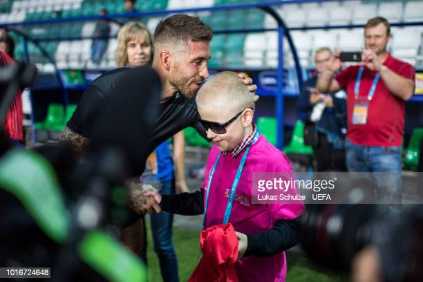 TALLINN ESTONIA AUGUST Sergio Ramos of Real Madrid kisses a blind boy of the UEFA Foundation after giving him his shirt after Real Madrid's training...