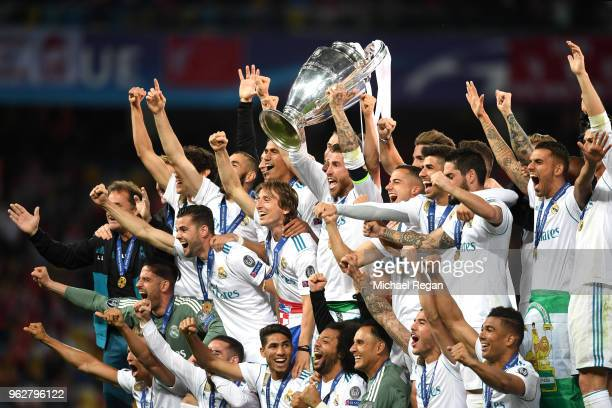 Sergio Ramos of Real Madrid lifts The UEFA Champions League trophy as his teammates celebrate following their sides victory in the UEFA Champions...