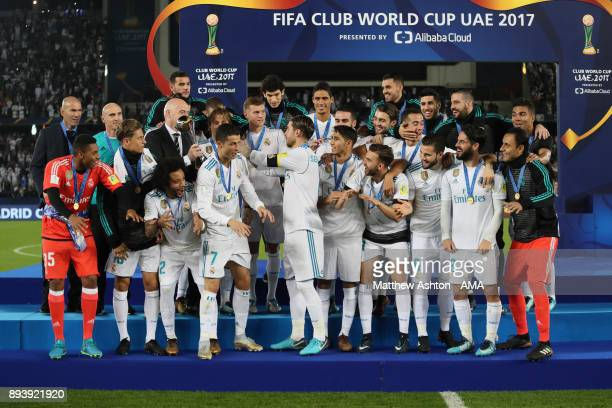 Sergio Ramos of Real Madrid receives the trophy from FIFA President Gianni Infantino at the end of the FIFA Club World Cup UAE 2017 final match...