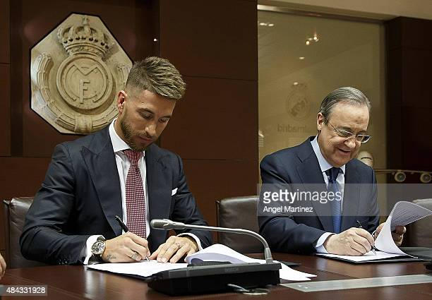 Sergio Ramos of Real Madrid signs his new fiveyear contract with Real beside president Florentino Perez at the Santiago Bernabeu stadium on August 17...