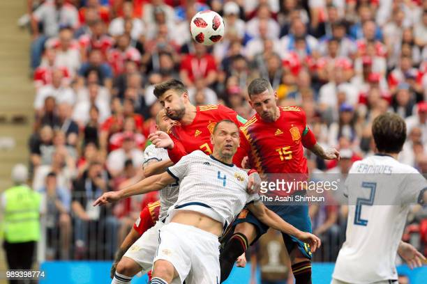 Sergio Ramos of Spain and Sergei Ignashevich of Russia compete for the ball during the 2018 FIFA World Cup Russia Round of 16 match between Spain and...