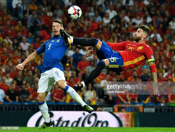 Sergio Ramos of Spain clears the ball under a challenge by Andrea Belotti of Italy during the FIFA 2018 World Cup Qualifier between Spain and Italy...