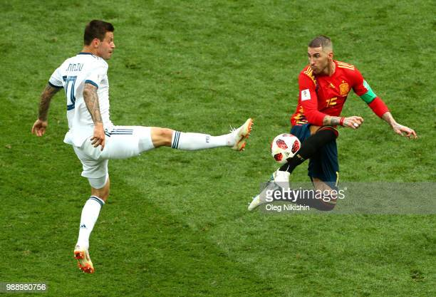 Sergio Ramos of Spain is challenged Fedor Smolov of Russia during the 2018 FIFA World Cup Russia Round of 16 match between Spain and Russia at...
