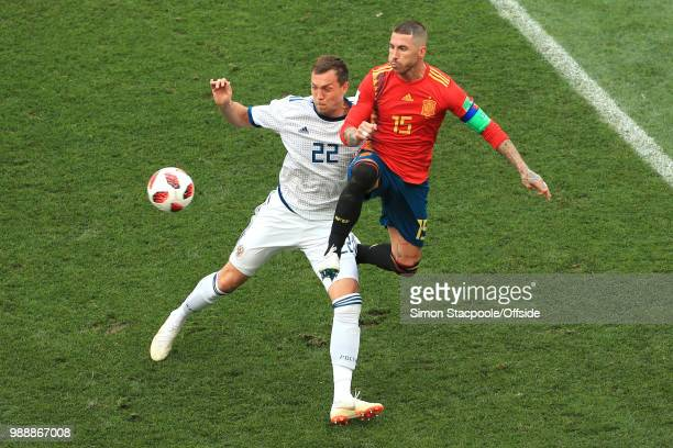 Sergio Ramos of Spain leaps across Artem Dzyuba of Russia for the ball during the 2018 FIFA World Cup Russia Round of 16 match between Spain and...