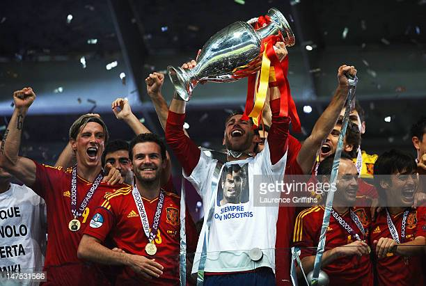 Sergio Ramos of Spain lifts the trophy next to team-mates Fernando Torres, Juan Mata, Andres Iniesta and David Silva as they celebrates following...