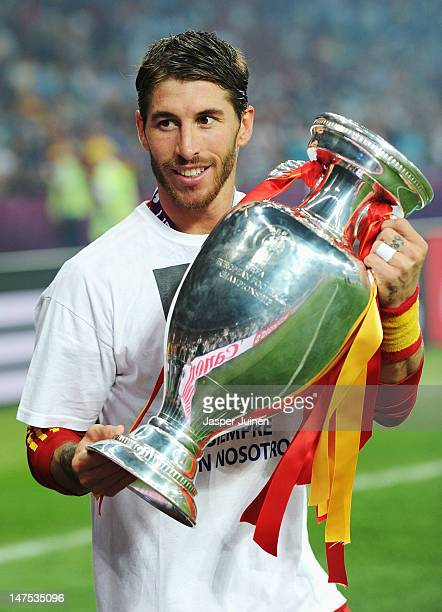 Sergio Ramos of Spain poses with the trophy following victory in the UEFA EURO 2012 final match between Spain and Italy at the Olympic Stadium on...
