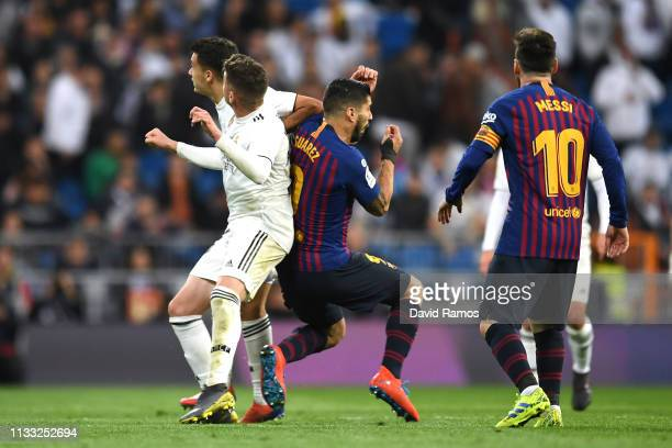 Sergio Reguilon of Real Madrid and Luis Suarez of Barcelona clash during the La Liga match between Real Madrid CF and FC Barcelona at Estadio...