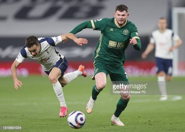 Sergio Reguilon of Tottenham Hotspur battles for possession with Oliver Burke of Sheffield United during the Premier League match between Tottenham...