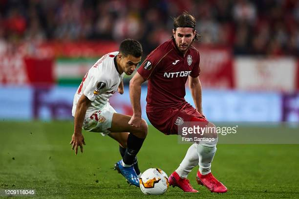 Sergio Reguilon Rodriguez of Sevilla FC competes for the ball with Alexandru Paun of CFR Cluj during the UEFA Europa League round of 32 second leg...