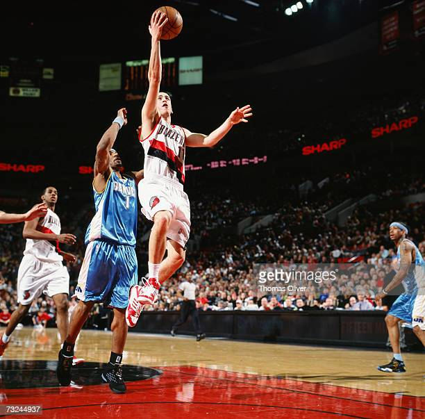 Sergio Rodriguez of the Portland Trail Blazers drives to the basket for a layup against JR Smith of the Denver Nuggets during a game at The Rose...