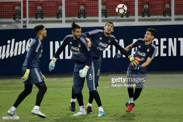 Sergio Romero challenges for the ball with teammates during an Argentina training session at National Stadium on June 12 2017 in Singapore Argentina...