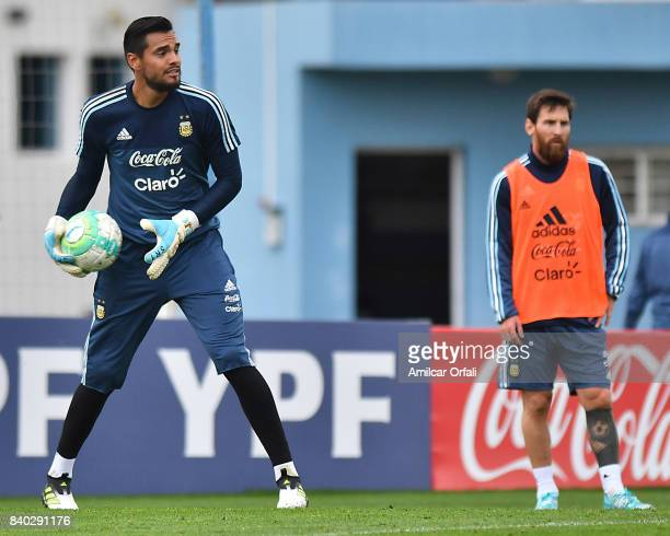 Sergio Romero goalkeeper of Argentina holds the ball as Lionel Messi of Argentina looks on during a training session at 'Julio Humberto Grondona'...