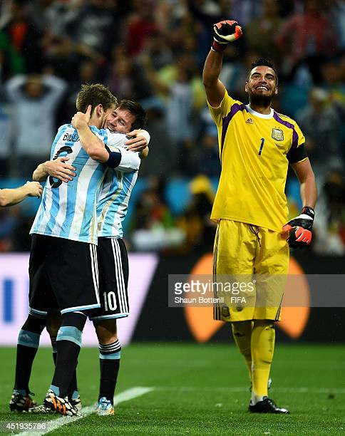 Sergio Romero Lionel Messi and Lucas Biglia of Argentina celebrate the win on penalties after the 2014 FIFA World Cup Brazil Semi Final match between...