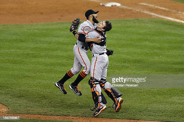 Sergio Romo of the San Francisco Giants celebrates with Buster Posey after striking out Miguel Cabrera of the Detroit Tigers in the tenth inning to...
