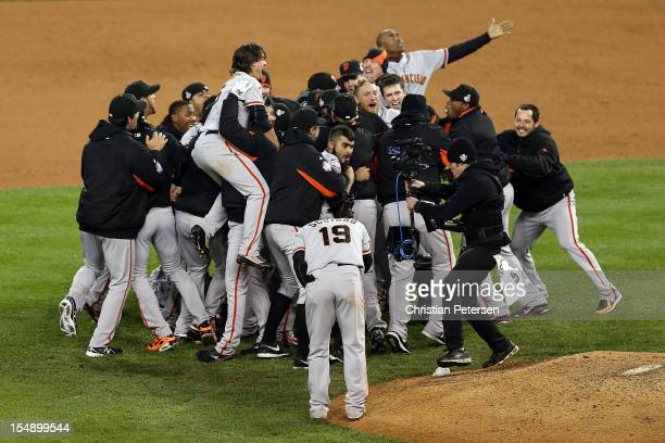 Sergio Romo of the San Francisco Giants celebrates with his teammates after striking out Miguel Cabrera of the Detroit Tigers in the tenth inning to...
