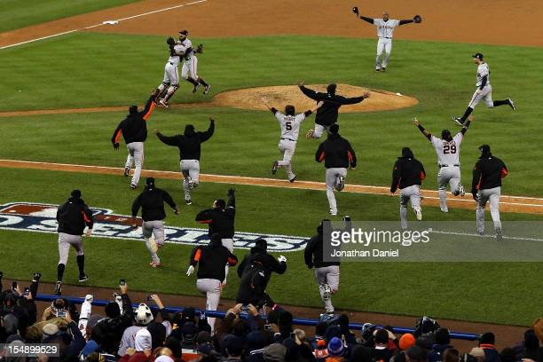 Sergio Romo of the San Francisco Giants hugs Buster Posey and teammates after striking out Miguel Cabrera of the Detroit Tigers in the tenth inning...