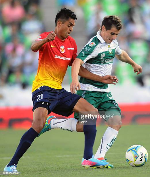 Sergio Santana of Morelia vies for the ball with Jorge Estrada of Santos during their 2013 Mexican Clausura tournament football match in Torreon...