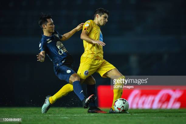 Sergio Suárez of Port FC and Jakkaphan Kaewprom of Buriram United are seen in action during the Thai League 2020 match between Buriram United and...