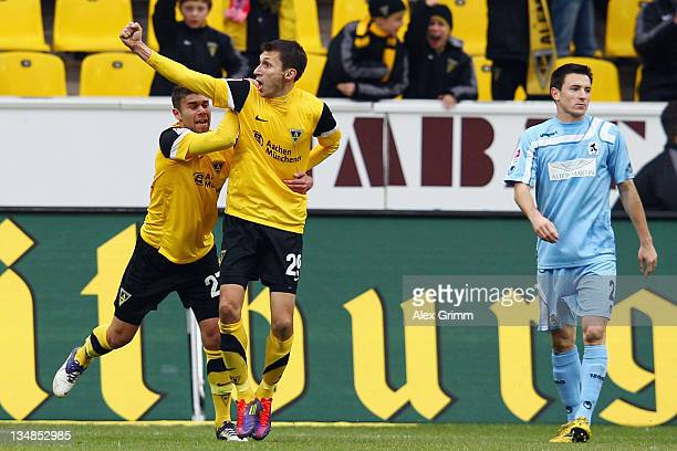 Sergiu Radu of Aachen celebrates his team's first goal with team mate Shervin RadjabaliFardi as Antonio Rukavina of Muenchen reacts during the Second...
