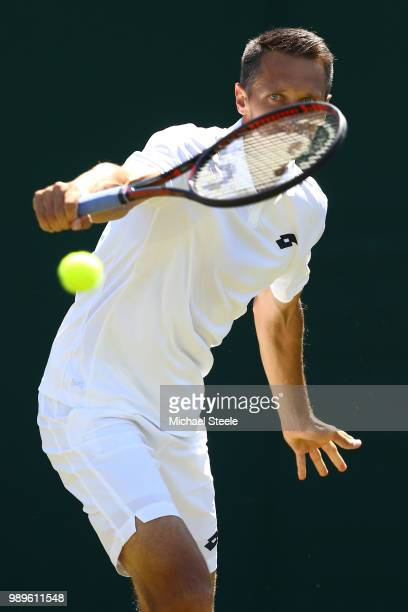 Sergiy Stakhovsky of Ukraine returns to Joao Sousa of Portugal during their Men's Singles first round match on day one of the Wimbledon Lawn Tennis...