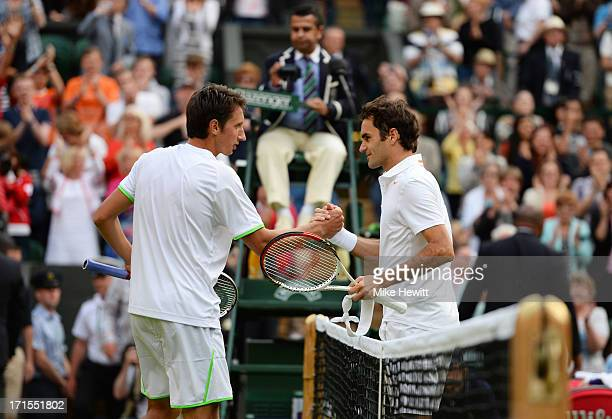 Sergiy Stakhovsky of Ukraine shakes hands at the net with Roger Federer of Switzerland after their Gentlemen's Singles second round match on day...