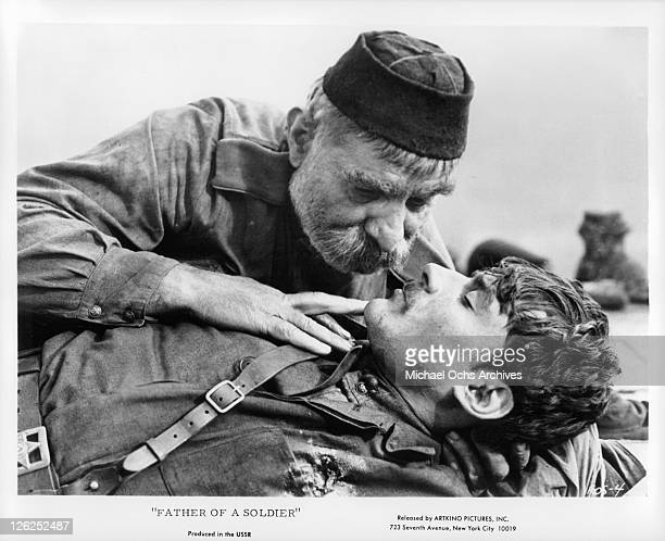 Sergo Zagariadze leaning over dead soldier in a scene from the film 'Father of A Soldier' 1964