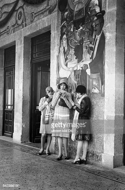 Serie Besuch in mexikanischenKunstschulenDrei junge Mädchen schminken sicham Eingang des UnterrichtsministeriumsDie Wand dahinter ist bemalt...