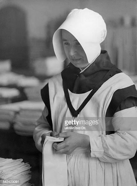 Serie: Das Kloster vom Guten Hirten - ein Wohltätigkeitsstaat innerhalb der Großstadt: Consecrierte Nonne beim Ordnen der Wäsche- 1930- Fotografie:...