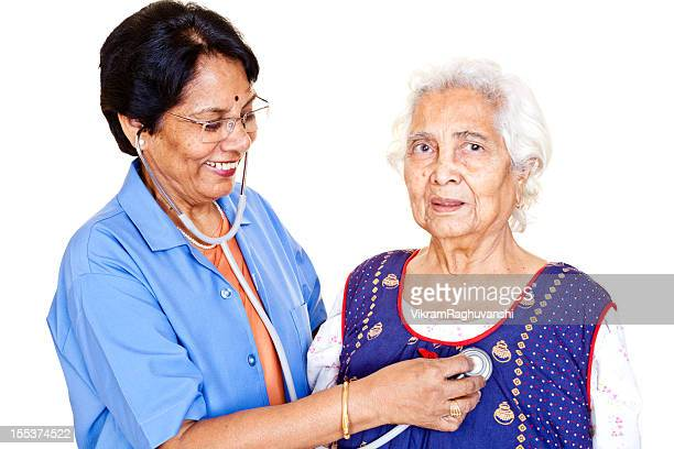 series - cheerful senior indian female doctor examining aged patient - nurse and portrait and white background and smiling and female and looking at camera stock pictures, royalty-free photos & images