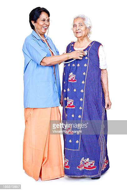 series... cheerful senior indian female doctor examining old aged patient - nurse and portrait and white background and smiling and female and looking at camera stock pictures, royalty-free photos & images