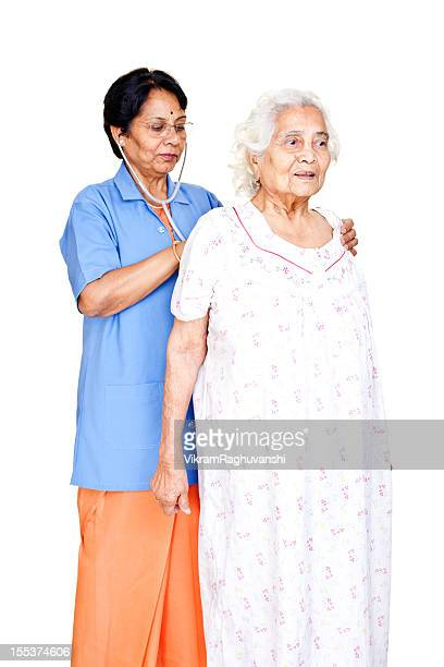 series - cheerful senior indian female doctor examining old patient - nurse and portrait and white background and smiling and female and looking at camera stock pictures, royalty-free photos & images