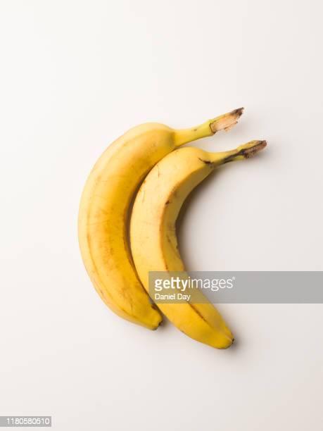 series of banana's against a white background - abbracciarsi a letto foto e immagini stock