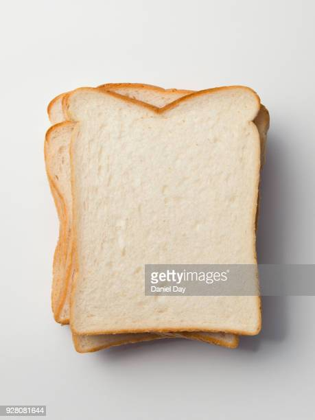 Series of different sliced white bread slices, some with butter, crust and pile of slices against a white background shot from above