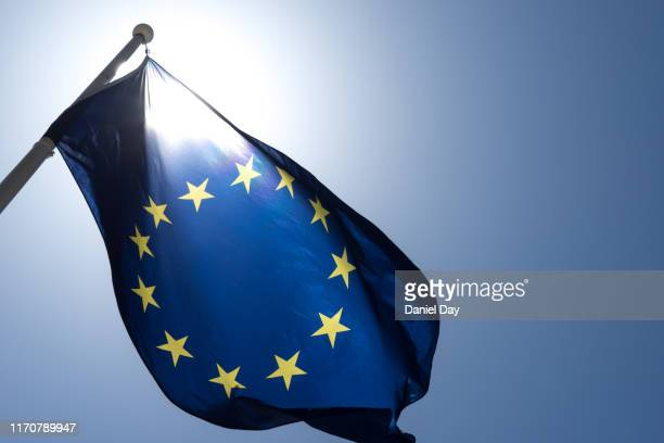 series of images of the eu flag flying in the wind, backlight and blue sky - contortionist stock pictures, royalty-free photos & images
