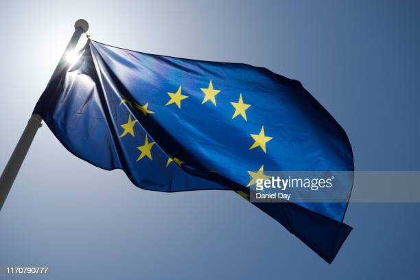 series of images of the eu flag flying in the wind, backlight and blue sky - europe stock-fotos und bilder