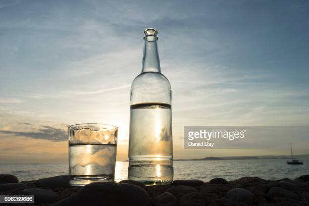 series of images with a bottle and glass of water with setting sun and sea in background - agua purificada fotografías e imágenes de stock