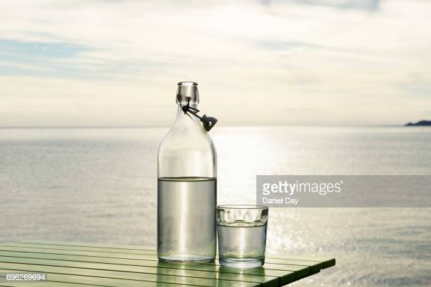 Series of images with a bottle and glass of water with setting sun and sea in background