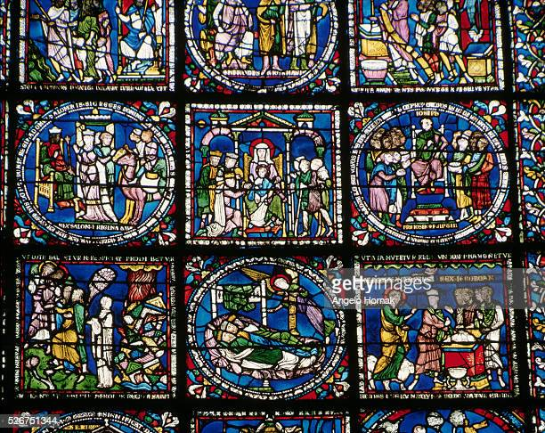 A series of stained glass panels from Canterbury Cathedral In the center panel Christ is depicted on Mary's knee with the 3 Magi visiting below this...