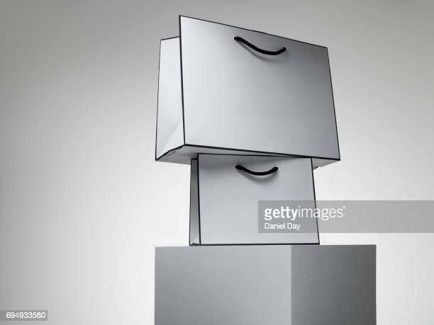 A series of white shopping bags stacked on a white plinth against a grey background