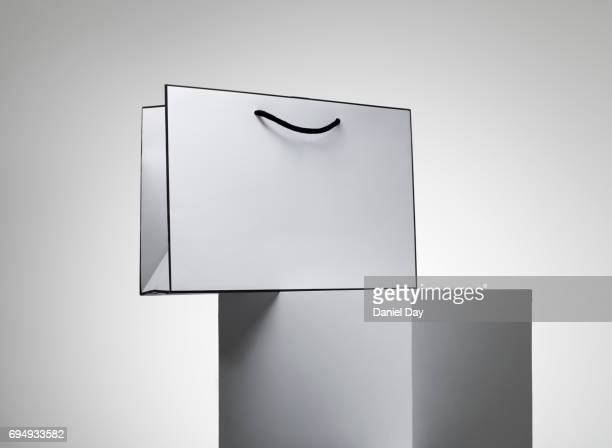 a series of white shopping bags stacked on a white plinth against a grey background - bag stock pictures, royalty-free photos & images